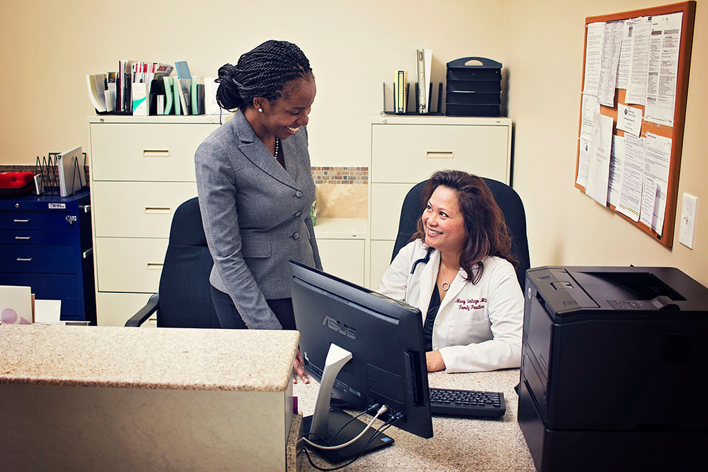 Dr. Mary Santiago, right, confers with Preferred Urgent Care Chief Executive Officer Dr. Ebun Ebunlomo